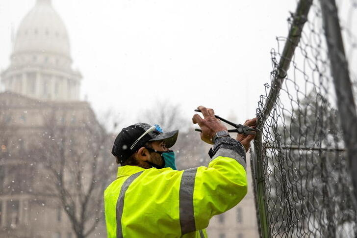 Fencing is put up around Lansing City Hall amid beefed up security ahead of planned protests at the state Capitol building in Lansing, Michigan, U.S., January 15, 2021. REUTERS/Emily Elconin